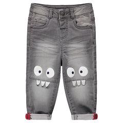 Vaqueros grises con efecto desgastado y arrugado con monstruos estampados en las rodillas